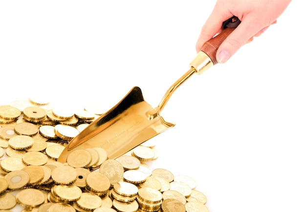 A hand with small shovel taking golden coins from a pile over white