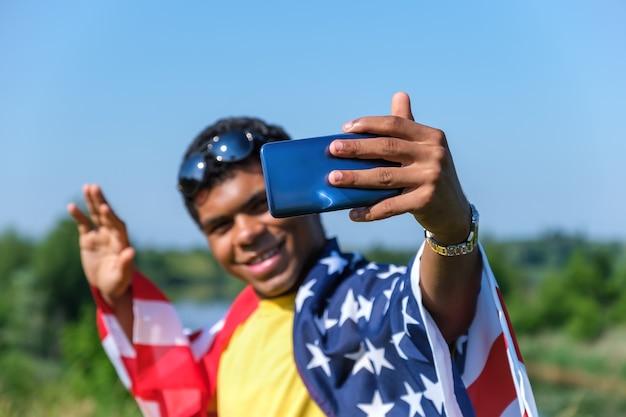 셀카를 찍는 미국 국기로 덮인 젊은 남자의 스마트폰으로 손
