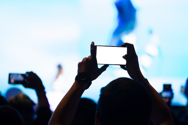 Hand with a smartphone records concert