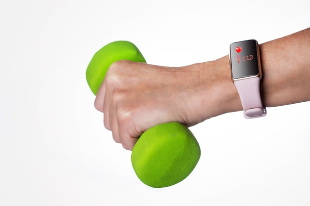 Hand with smartwach during exercise on light gray background.