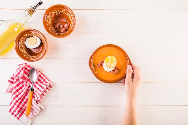 Рука с плитой супа на столе для приготовления пищи
