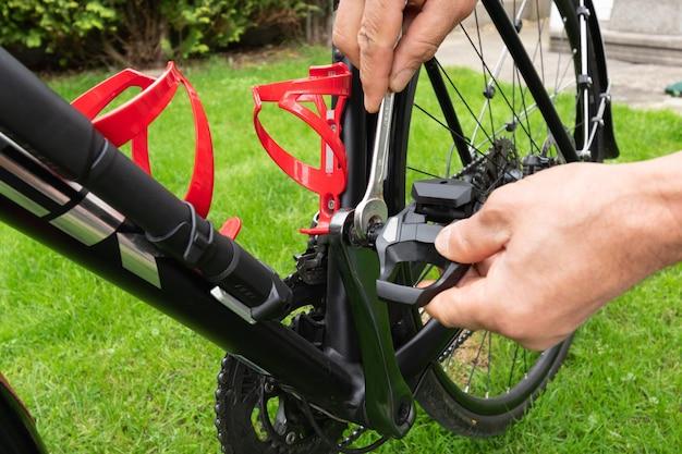 芝生に自転車のペダルを取り付けているスパナ付きの手