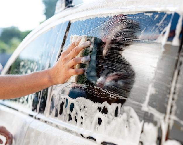 Рука с губкой и пеной для мытья окон автомобиля