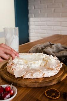 Hand with spoon decorating meringue cake