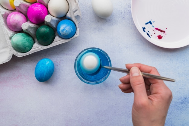 Hand with spoon near glass of water and easter eggs in container