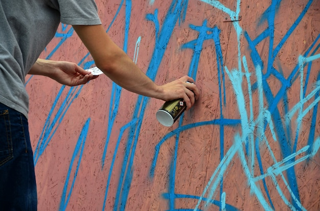 A hand with a spray can that draws a new graffiti on the wall