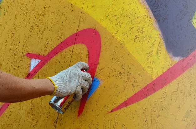 A hand with a spray can that draws a new graffiti on the wall.