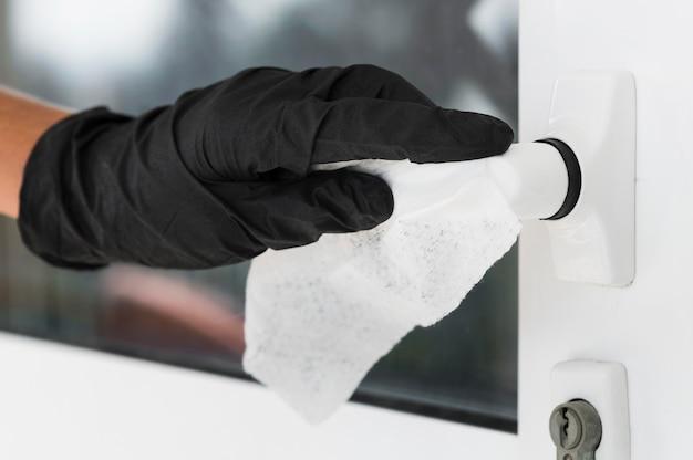 ドアハンドルを消毒する手術用手袋の付いた手