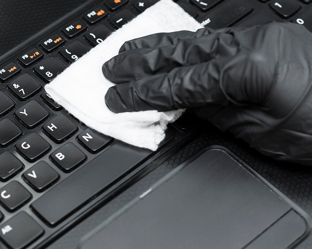 Hand with surgical glove disinfecting laptop keyboard