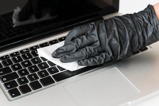 Hand with surgical glove disinfecting laptop surface