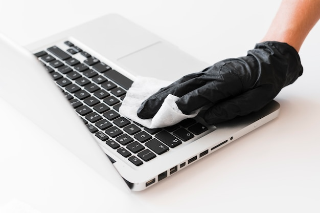 Hand with surgical glove disinfecting laptop