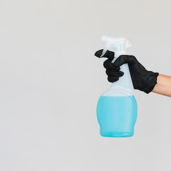 Hand with surgical glove holding cleaning solution bottle with copy space