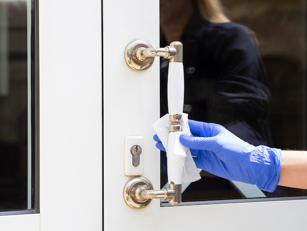 Hand with surgical gloves disinfecting door handle
