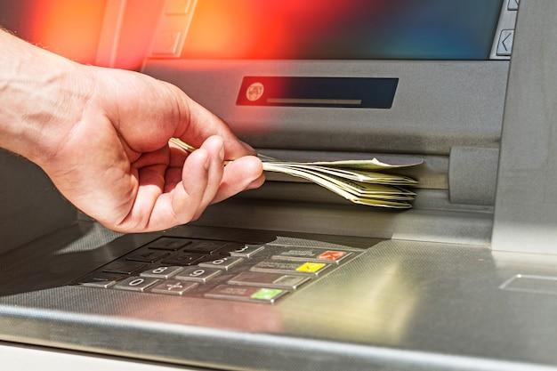 Atmからお金を持って手に取ってください。 atm銀行銀行紙幣銀行窓口係が通貨を削除する