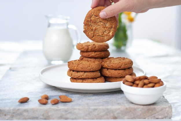 Рука с вкусным овсяным миндальным печеньем с банкой молока на старом мраморном столе