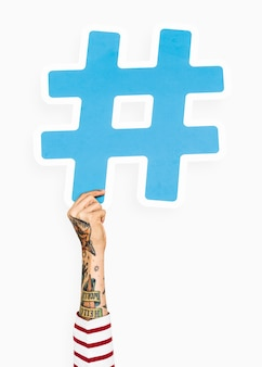 Hand with tattoo holding hashtag icon