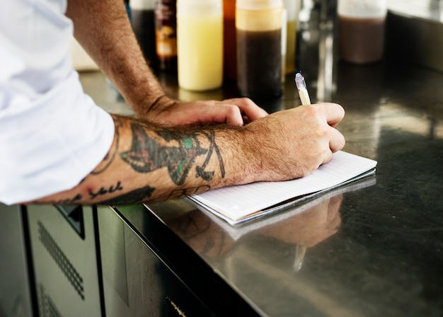 Hand with tattoo writing down an invetory in the kitchen