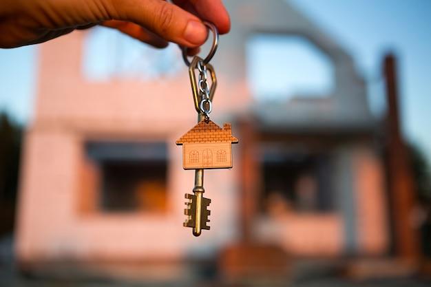 건설 현장 배경에 있는 미래 집의 열쇠와 다공성 콘크리트 블록으로 만든 벽을 손에 넣으세요. 집 짓기, 새 오두막으로 이사하기, 시골에서 농장