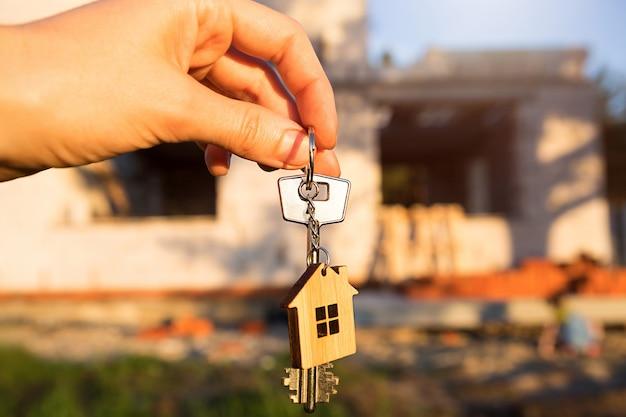 건설 현장과 벽을 배경으로 미래 집 열쇠를 들고
