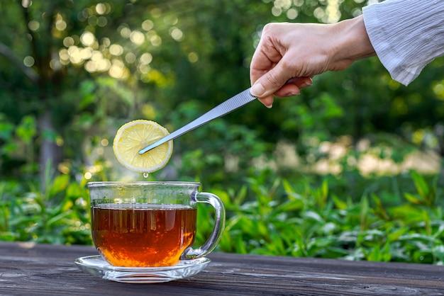 Рука с щипцами кладет лимон в чай в стеклянной чашке на деревянном столе