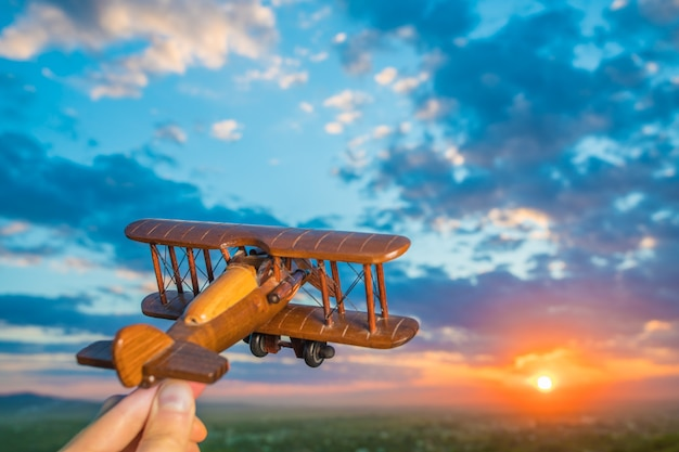 The hand with a toy airplane against the background of a sunset