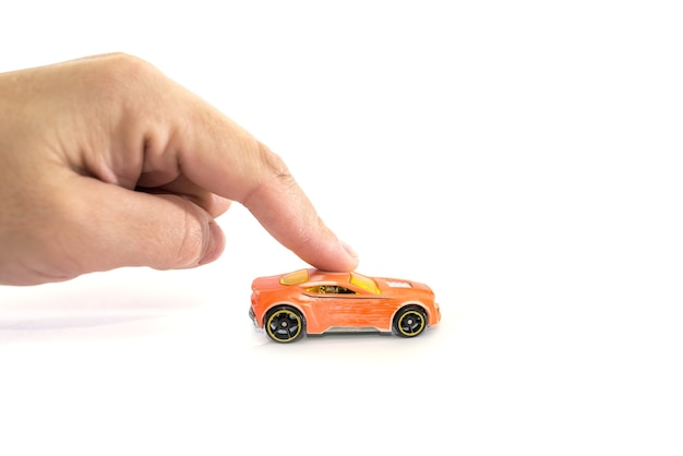 Hand with toy car isolated on white surface