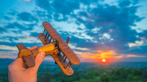The hand with a toy plane against the background of a sunrise