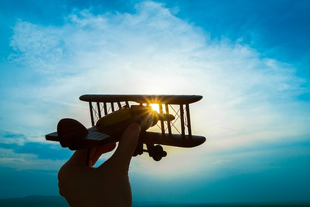 The hand with a toy plane on the background of the sunrise
