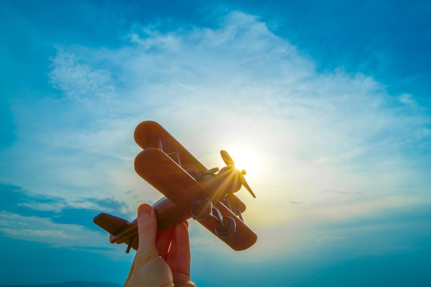 The hand with a toy plane on the background of the sunset