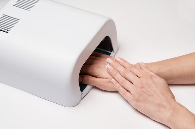 Рука с уф-лампой таймера освещает ногти на светлой поверхности