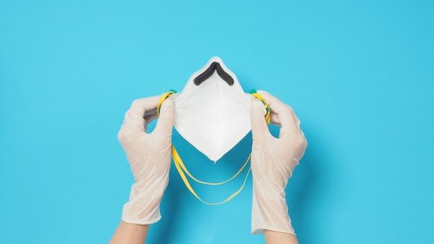 바이러스 감염으로부터 보호하기 위해 흰 장갑과 n 95 얼굴 마스크를 손에 넣으세요. 파란색 배경에 두세요.
