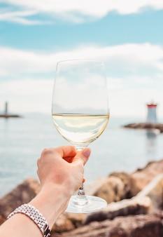 海の石とフランスの灯台の背景に白ワイングラスと手