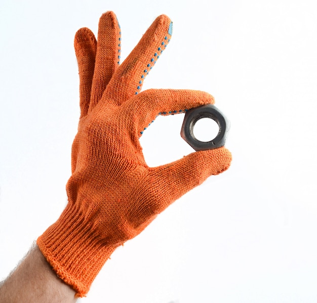A hand with working gloves holds a metal nut.