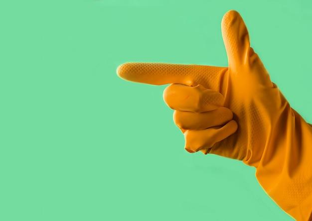 노란색 고무 장갑 손으로 녹색 파스텔 배경에 측면을 가리키는
