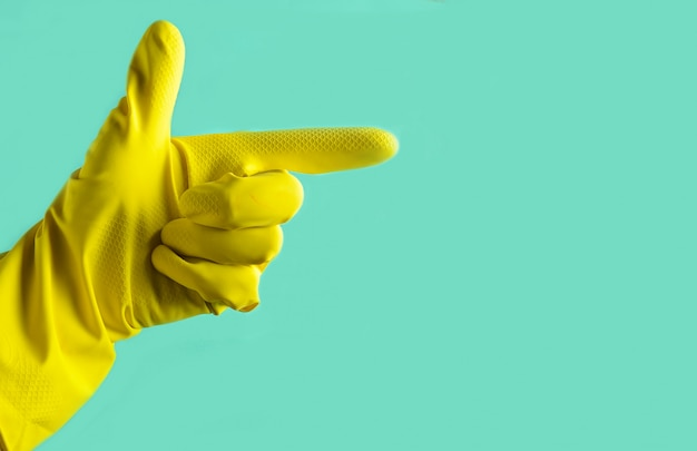 Hand with yellow rubber glove is pointing in the side, cleaning concept, copy space
