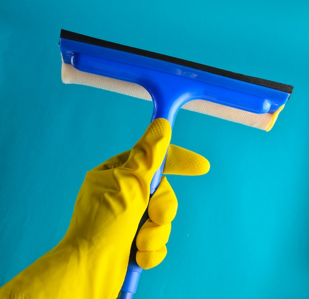 A hand with yellow rubber gloves holds a window mop. cleaning concept
