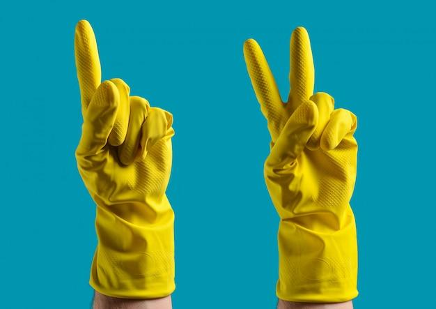 黄色のゴム手袋をはめた手が1つと2つを示す