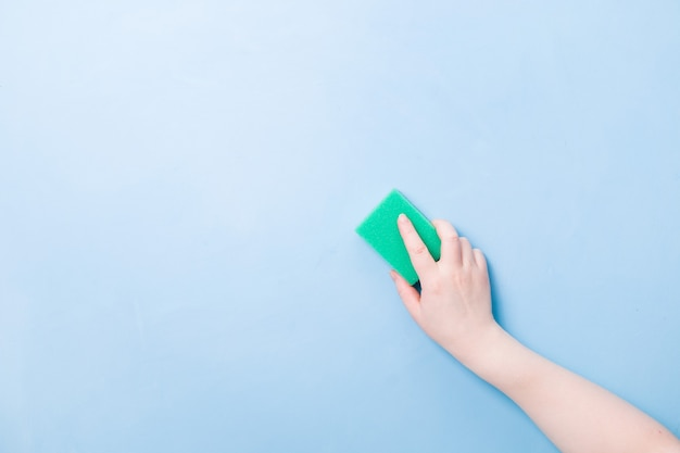 Hand without a glove holds a green sponge for washing dishes and cleaning