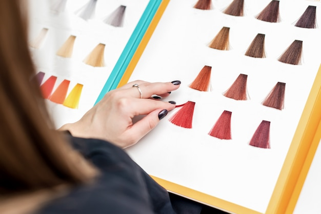 Hand of woman choosing red hair samples from palette