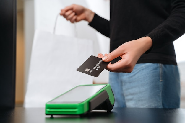 Hand of woman customer using wireless or contactless payment by credit card, girl making shopping.