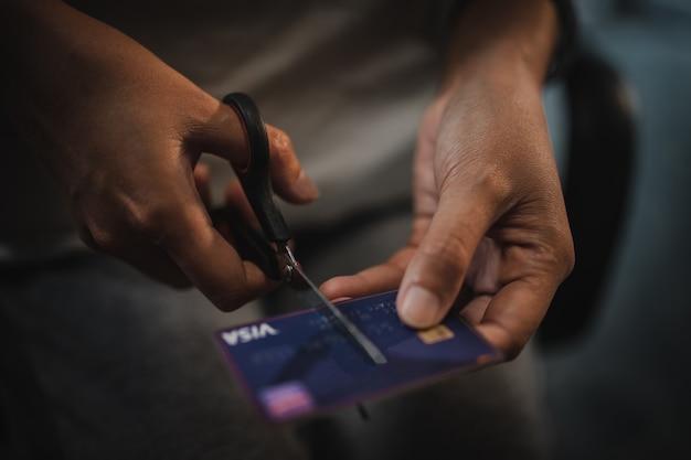 はさみで金のクレジットカードを切る手の女性。