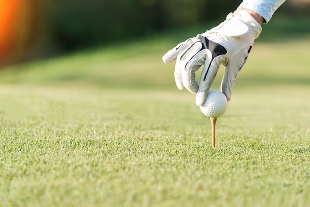 Hand of woman golf playerpush wooden tee with golf ball on the grass tee off, to be ready for hit th