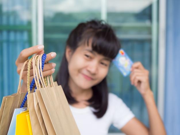 紙袋とクレジットカードを保持している手の女性。