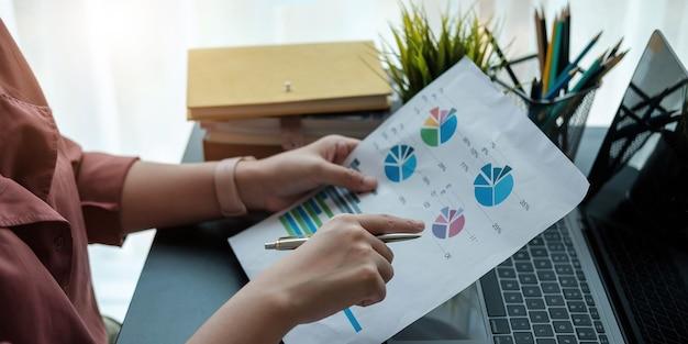 Вручите женщину, держащую ручку, указывая на диаграмму сводного отчета и рассчитайте финансы.