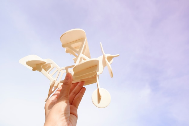 Hand woman holding toy airplane against sky. background , image is retro filtered