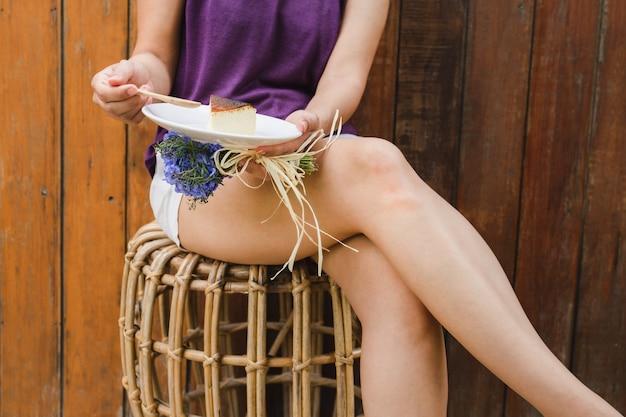 バスクの焦げたチーズケーキを食べるための木のスプーンを保持している女性を手します。