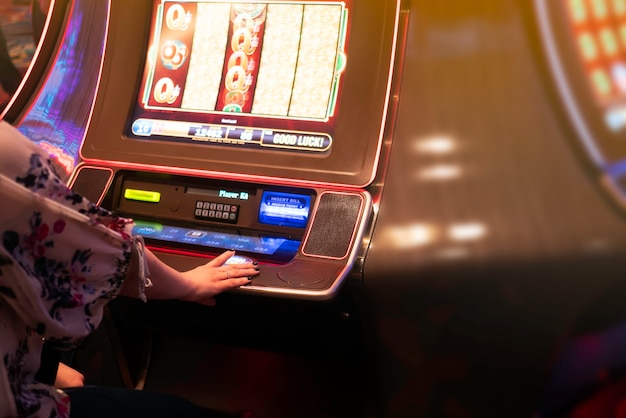 Hand of woman playing slot machine in casino.