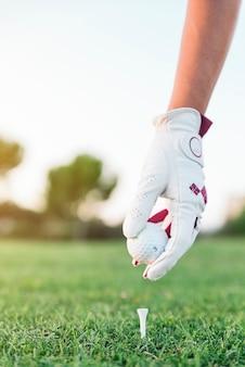 Рука женщина кладет мяч для гольфа на тройник. концепция гольфа.