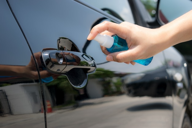 Hand of woman spraying alcohol,disinfectant spray on handle of car door. prevent infection covid-19