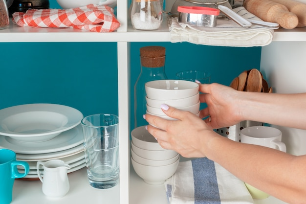 Hand of a woman taking kitchenware from a kitchen shelf